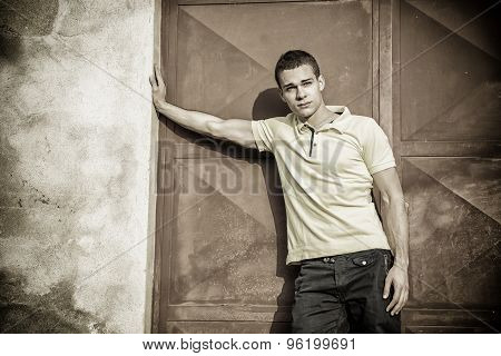Attractive green eyed young man leaning against wall outside