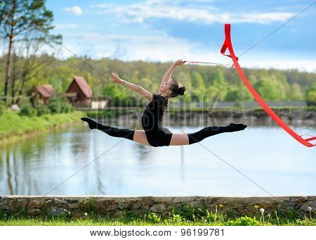 Rhythmic gymnast girl exercising with ribbon outdoor