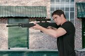 stock photo of rifle  - Handsome man holding an automatic assault rifle - JPG