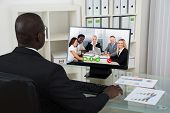 stock photo of video chat  - Young African Businessman Video Chatting With Colleagues On Computer In Office - JPG