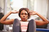 stock photo of crunch  - Young woman doing crunches in a gym - JPG