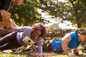 picture of crawl  - Assault course competitor helping others crawl under nets - JPG