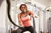 picture of roping  - Young woman working out with battle ropes at a gym - JPG