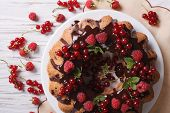 foto of sponge-cake  - Homemade berry sponge cake with chocolate icing on a plate closeup - JPG