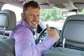 stock photo of steers  - Handsome young businessman is giving thumbs up and smiling - JPG