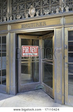 Entrance door of closed newspaper office and 'for rent' sign