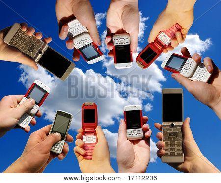 Muchas manos sosteniendo los teléfonos móviles