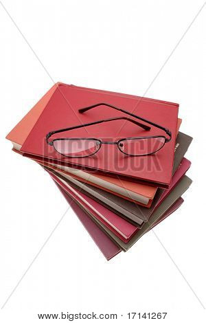 Reading glasses on pile of books, isolated on white
