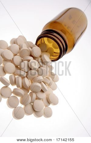 Pills spilling from bottle over white