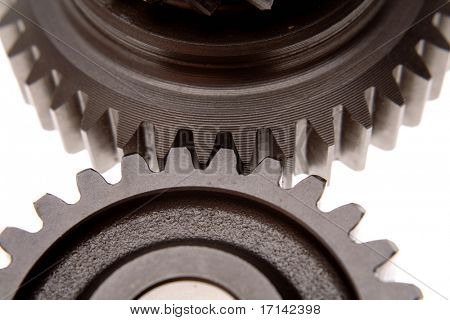 Two gears connecting together over white