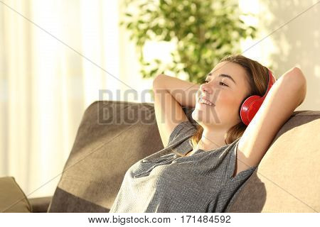 poster of One relaxed teen resting and listening music with wireless headphones sitting on a sofa in the living room at home with a warm light