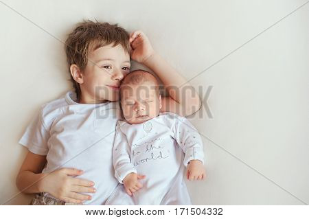 797bba86f3eb Little brother hugging her newborn baby. Toddler kid meeting new ...