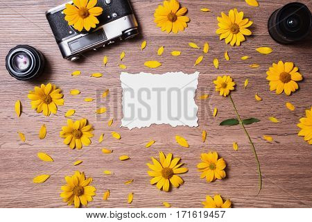 White sheet of paper and yellow summer flowers on a wooden vintage background. Vintage camera and lenses. Workplace photographer. Space for text. Old appliances. Charred card.