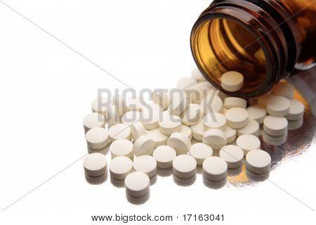 Pills spilling from bottle on white