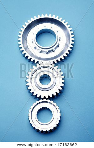 Three cogs on blue background