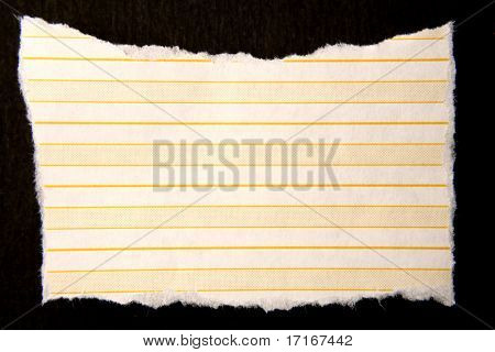 Ripped lined paper over dark surface