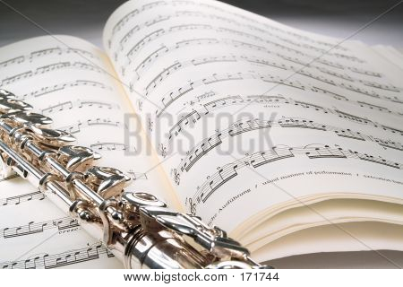 Flute On An Open Musical Score With Gray Background