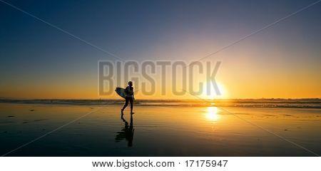 Surfer Walks Down Beach at Sunset