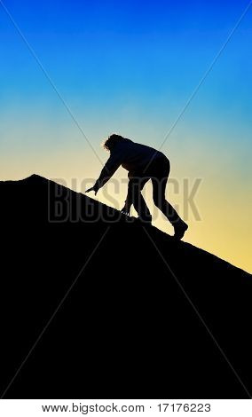 Silhouette of Man Climbing To Top of a Mountain
