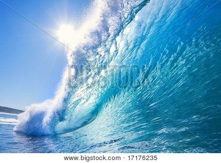 Onda surf azul grande quebra no oceano com sol e céu claro, perspectiva na surfista