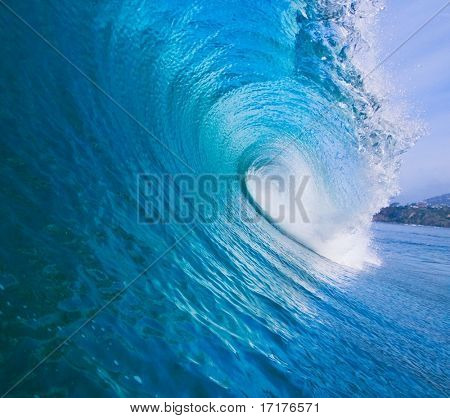 Large Blue Surfing Wave Breaks in the Ocean