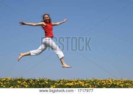 Girl Flying In A Jump Over Dandelion Field