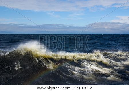 Waterscape with rainbow from waves splashes