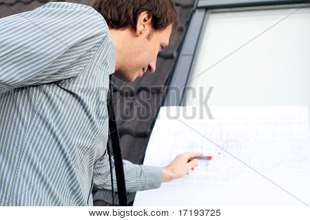 Young Man Architect Presenting A Project Against The Background Of The Roof And Windows