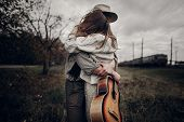 Stylish Hipster Couple Dancing In Windy Field. Boho Gypsy Woman And Man In Hat Embracing In Windy Fi poster