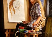 Artist painting on easel in studio. Girl paints portrait of woman with brush. Female painter seen fr poster