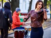 Violin woman outdoor. Festival music band. Friends playing on percussion instruments in city park. C poster