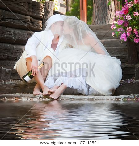 Beautiful newly wed couple having a drink outdoors with a bottle of champagne