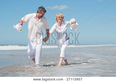 Senior smiling couple running on beach, hand in hand.
