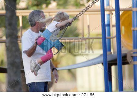 Hombre empujando la niña en un columpio
