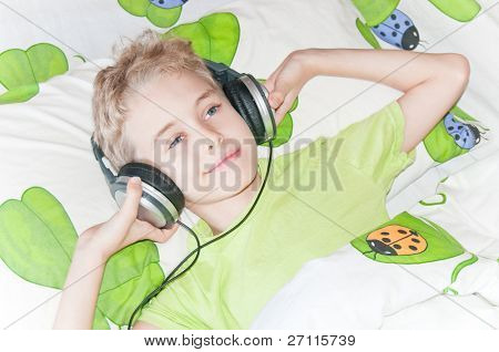 Little boy listening music with headphones on lying on his bed