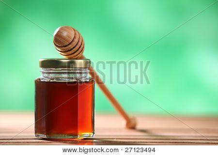 honey muddler resting on top bottle of honey