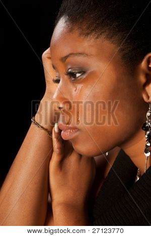 Tears running of the face of a young african woman