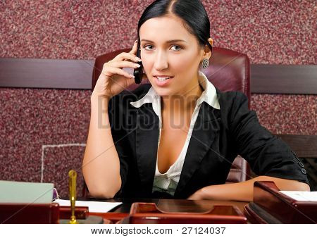 active young businesswoman in an office with telephone