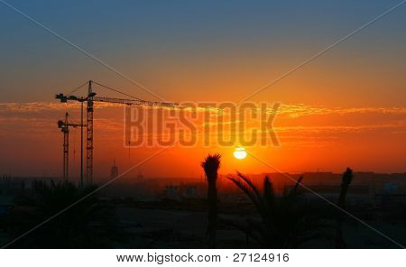 Construction crane over orange sunset sky