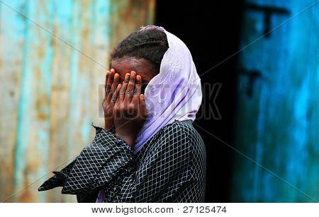 Afrika, Kenia, Sumburu November 7:portrait von einer afrikanischen Kind der Sumburu Stamm Dorf, spielen verbergen