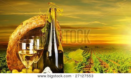 Wine. Romantic dinner outdoor, table for two with vineyard view, fresh grapes and wineglass at restaurant, warm autumn sunset, grape field landscape at harvest, food still life