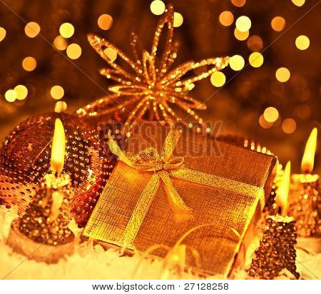Golden gift box with baubles decorations and candles, Christmas tree ornament for winter holidays, present with abstract bokeh shiny glowing blur lights background