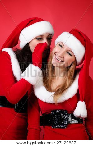 wo happy young Santa girl talking over red background .