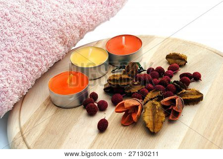 three candles with dried flowers in wooden dish