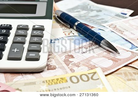 Pen and calculator on euro banknotes