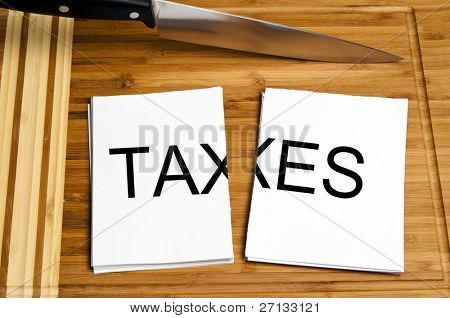 Knife cut paper with taxes word