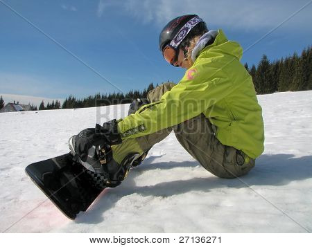 female snowboarder with helmet fastening bindings