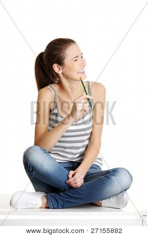 Front view portrait of a full length  caucasian female teen sitting on a table, holding a pencil and smiling to the site, on white.
