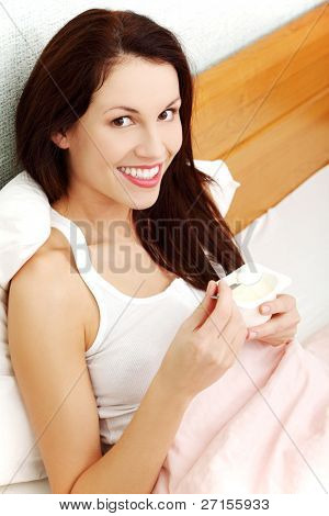Closeup of a beautiful young woman holding a small spoon with a yogurt, sitting in bed and smiling straight to the camera.
