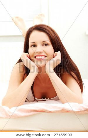 Front view picture of a young beautiful woman resting in the bed on her belly having a look at the camera, with a view on her feet in the back.